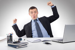 Homme d'affaires de sourire avec l'ordinateur portable et documents au bureau Image libre de droits