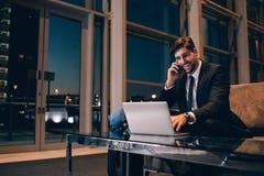 Homme d'affaires de sourire avec l'ordinateur portable parlant sur le téléphone portable à l'airp Photos stock
