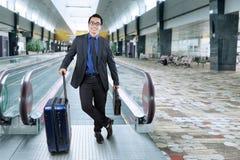 Homme d'affaires de sourire avec le bagage dans le hall d'aéroport Photographie stock libre de droits