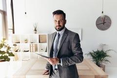 Homme d'affaires de sourire avec le comprimé numérique regardant l'appareil-photo Photo stock