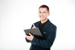 Homme d'affaires de sourire avec le presse-papiers regardant l'appareil-photo Images stock