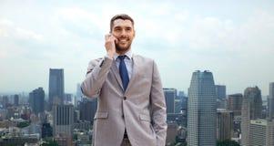 Homme d'affaires de sourire avec le smartphone dans la ville Image libre de droits