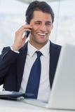 Homme d'affaires de sourire ayant un appel téléphonique Photographie stock