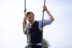 Homme d'affaires de sourire balançant dans les cordes Photo stock