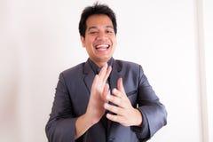 Homme d'affaires de sourire battant ses mains photos stock