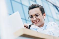 homme d'affaires de sourire bel dans des lunettes utilisant l'ordinateur portable dehors image libre de droits