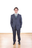 Homme d'affaires de sourire dans des poses occasionnelles de costume noir au studio Images stock