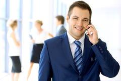Homme d'affaires de sourire dans le bureau avec des collègues à l'arrière-plan et à employer le mobile Photo stock