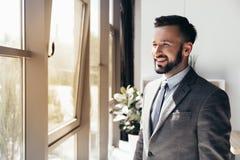Homme d'affaires de sourire dans le tenue de soirée regardant loin le bureau moderne Images libres de droits