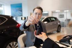 Homme d'affaires de sourire donnant des clés de voiture au client féminin images libres de droits