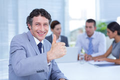 Homme d'affaires de sourire faisant des gestes des pouces  Photographie stock