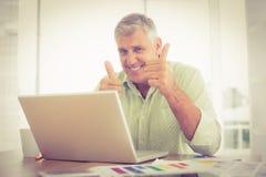 Homme d'affaires de sourire faisant des gestes des pouces  Images stock