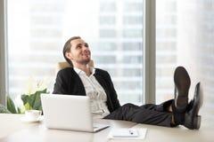 Homme d'affaires de sourire heureux détendant sur le lieu de travail dans le bureau moderne Photos libres de droits