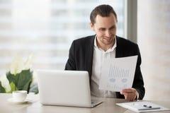 Homme d'affaires de sourire heureux dans le bureau regardant le rapport financier Images stock