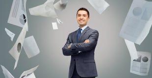 Homme d'affaires de sourire heureux dans le costume au-dessus des papiers Photos stock