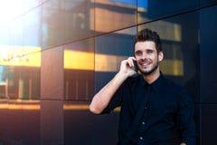 Homme d'affaires de sourire heureux habillé dans le tenue de soirée parlant avec l'associé par l'intermédiaire du téléphone porta photographie stock