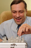 Homme d'affaires de sourire jouant aux échecs Photo stock