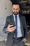 Homme d'affaires de sourire jugeant le smartphone disponible Photographie stock libre de droits