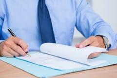 Homme d'affaires de sourire lisant un contrat avant de le signer Photographie stock libre de droits