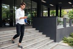 Homme d'affaires de sourire marchant et à l'aide du téléphone portable près du centre d'affaires photos stock