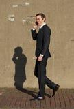 Homme d'affaires de sourire marchant et parlant sur le téléphone portable Image libre de droits
