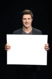 Homme d'affaires de sourire montrant la carte vierge d'isolement sur le noir Photos libres de droits