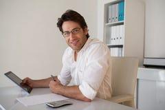 Homme d'affaires de sourire occasionnel utilisant le comprimé et la calculatrice image libre de droits
