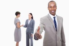 Homme d'affaires de sourire offrant sa main avec le colleagu de secousse de main Photo stock