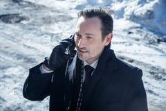 Homme d'affaires de sourire parlant au téléphone, jour Photographie stock libre de droits