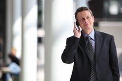 Homme d'affaires de sourire parlant au téléphone pendant un voyage d'affaires Photographie stock