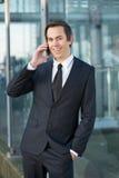Homme d'affaires de sourire parlant au téléphone portable dehors Photos libres de droits