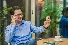 Homme d'affaires de sourire parlant avec le téléphone intelligent et donner la carte au serveur en café Photographie stock