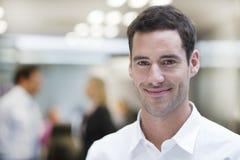 Homme d'affaires de sourire posant tandis que collègues parlant ensemble dedans Image libre de droits