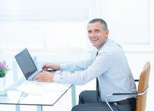 Homme d'affaires de sourire réussi travaillant sur l'ordinateur portable au bureau dans l'offi Image stock