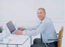 Homme d'affaires de sourire réussi travaillant sur l'ordinateur portable au bureau dans l'offi Images stock