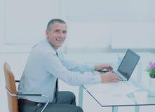 Homme d'affaires de sourire réussi travaillant sur l'ordinateur portable au bureau dans l'offi Image libre de droits