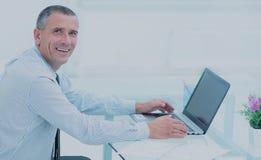 Homme d'affaires de sourire réussi travaillant sur l'ordinateur portable au bureau dans l'offi Photo libre de droits