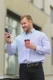 Homme d'affaires de sourire regardant à son téléphone portable dehors Images stock