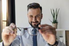 Homme d'affaires de sourire regardant des paires de lunettes dans des mains Photos stock