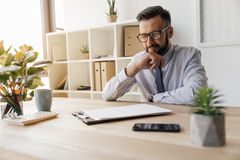 Homme d'affaires de sourire regardant le papier blanc sur la table dans le bureau Photographie stock