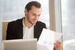 Homme d'affaires de sourire regardant le rapport financier sur le lieu de travail Photos libres de droits