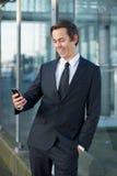 Homme d'affaires de sourire regardant le téléphone portable dehors Images stock