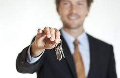 Homme d'affaires de sourire remettant des clés Photographie stock libre de droits