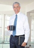 Homme d'affaires de sourire restant dans la configuration de bureau Image stock