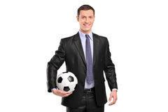 Homme d'affaires de sourire retenant un football Photos libres de droits