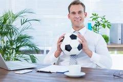 Homme d'affaires de sourire retenant un football Photos stock