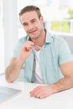 Homme d'affaires de sourire s'asseyant à son bureau tenant des verres Images libres de droits