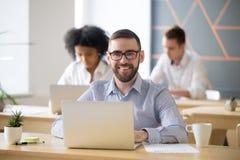 Homme d'affaires de sourire s'asseyant au bureau avec l'ordinateur portable dans le bureau, portr photo stock