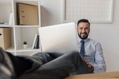 Homme d'affaires de sourire s'asseyant avec l'ordinateur portable sur des jambes et regarder l'appareil-photo Photographie stock libre de droits
