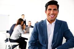 Homme d'affaires de sourire s'asseyant dans l'avant Image libre de droits